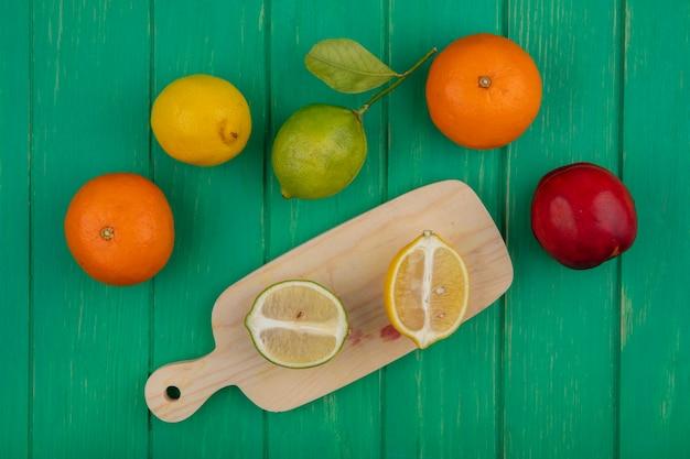 緑の背景のまな板にライムとレモンとオレンジのトップビュー