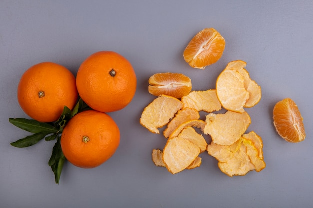 Top view oranges with peel on gray background