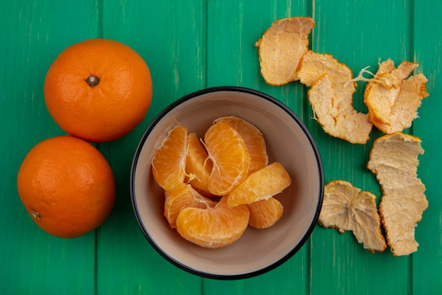 Vista dall'alto le arance sbucciate in una ciotola con le bucce su uno sfondo verde