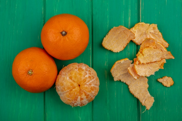Top view oranges with peeled peels on green background