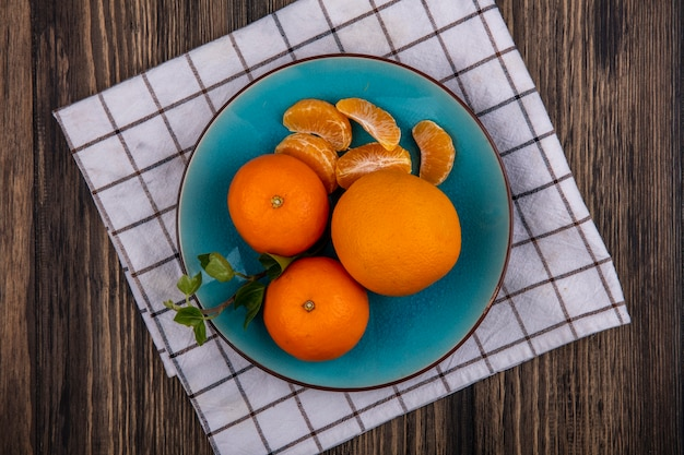 Top view oranges with peeled wedges on a blue plate on a checkered towel