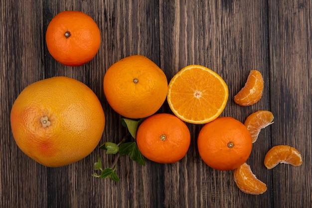 Vista dall'alto arance con spicchi sbucciati e pompelmo su fondo in legno