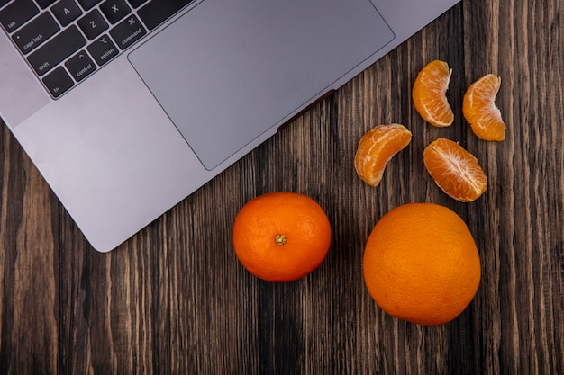Top view oranges with peeled wedges and a laptop on a wooden background