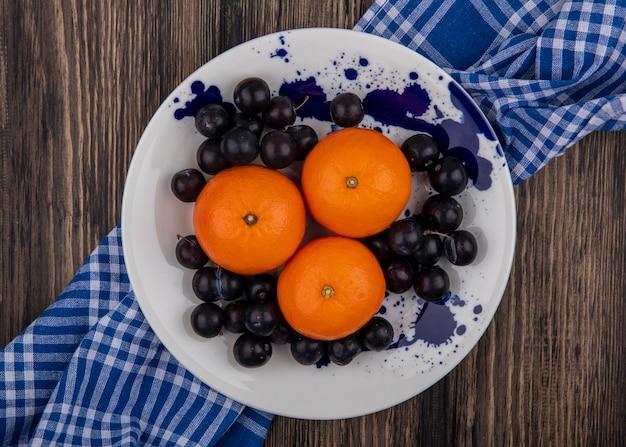 Vista dall'alto arance con prugne sul piatto bianco con asciugamano a scacchi blu su fondo in legno