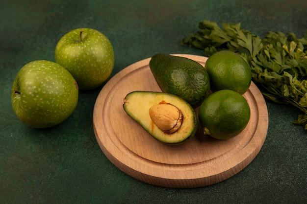Vista dall'alto di avocado biologici su una tavola di cucina in legno con limette con mele verdi e prezzemolo isolato su uno sfondo verde