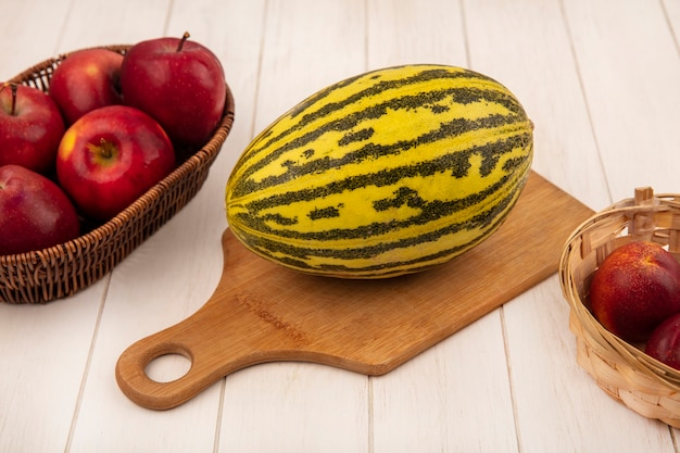 Top view of organic cantaloupe melon on a wooden kitchen board with apples on a bucket with peaches on a white wooden background