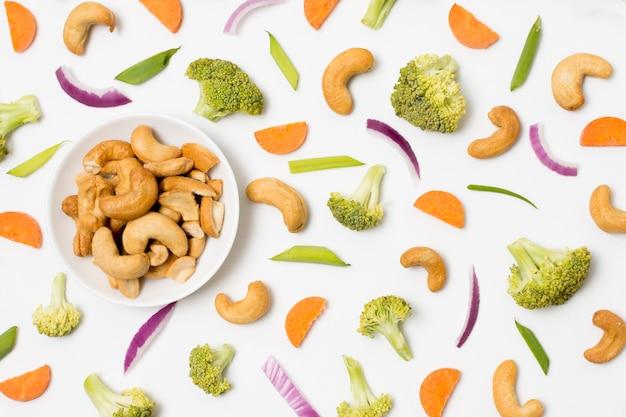 Vista dall'alto di anacardi e verdure biologici sul tavolo