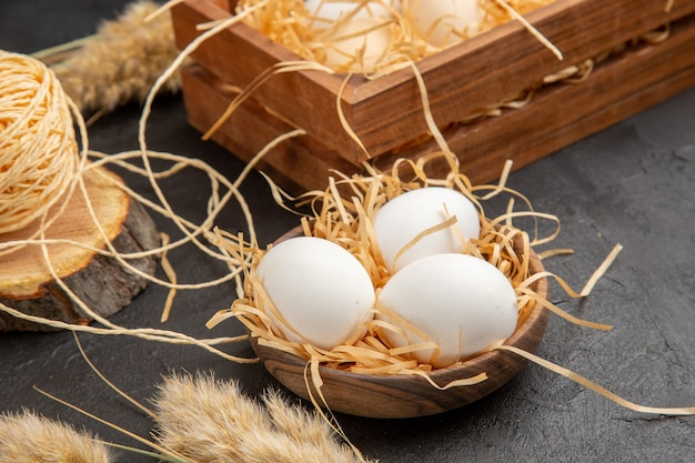 Top view of organic eggs in a brown pot spike yellow chaws on dark background
