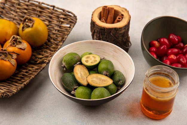Top view of organic feijoas on a bowl with persimmons on a wicker tray with cinnamon sticks with cornelian cherries on a bowl with honey on a glass jar on a grey background