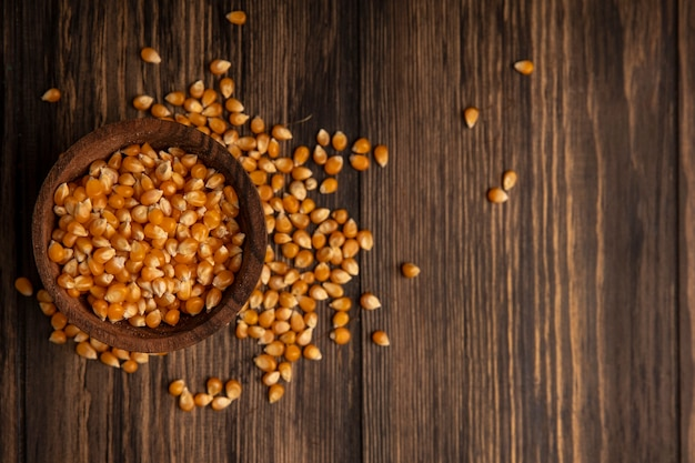 Top view of organic fresh corn kernels on a wooden bowl with corn kernels isolated on a wooden table with copy space