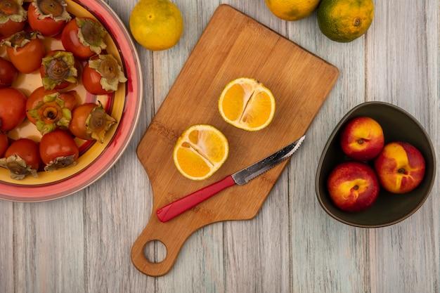 Vista dall'alto di mandarini freschi organici su una tavola da cucina in legno con coltello con pesche su una ciotola con cachi su un piatto su un fondo di legno grigio