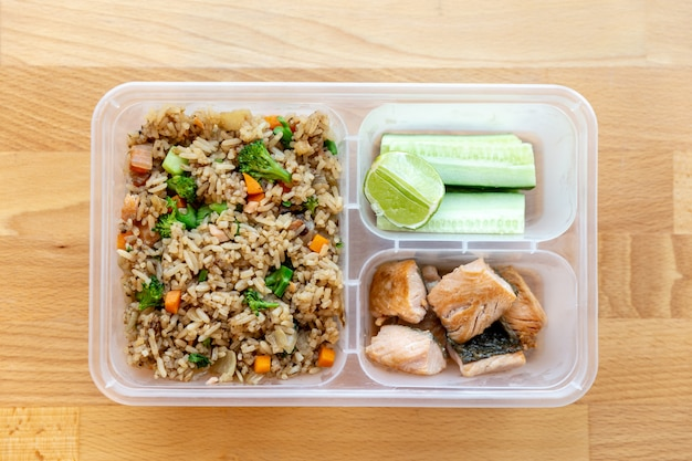 Top view of organic fried salmon diced steak with onion, broccoli and carrot fried rice.