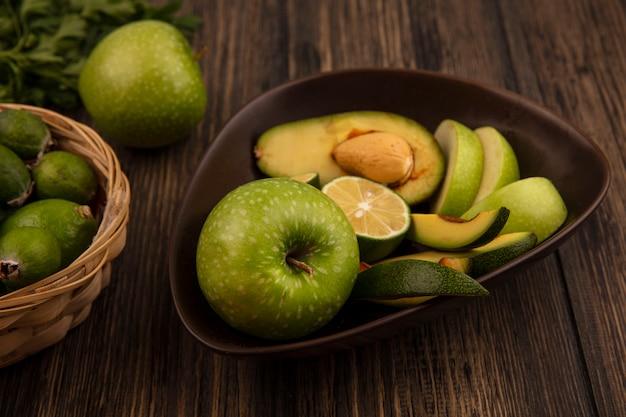 Vista dall'alto di fette di frutta organica come mele avocado limette su una ciotola con feijoas e limette su un secchio su una superficie in legno