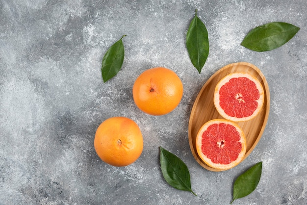 Top view of organic grapefruit whole or half cut with leaves.