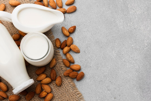 Top view organic milk and almonds with copy space