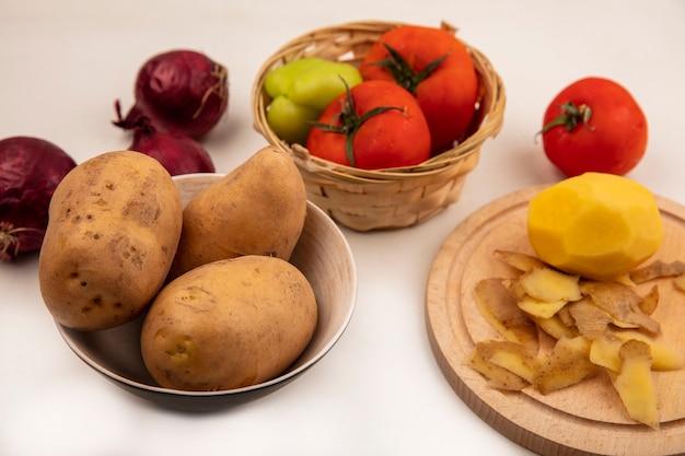 Vista dall'alto di patate pelate organiche su una tavola da cucina in legno con patate su una ciotola con pomodori e pepe su un secchio con cipolle rosse isolato su una superficie bianca