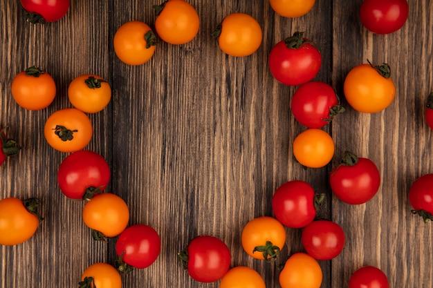 Vista dall'alto di pomodorini rossi e arancioni biologici isolati su una parete in legno con spazio di copia