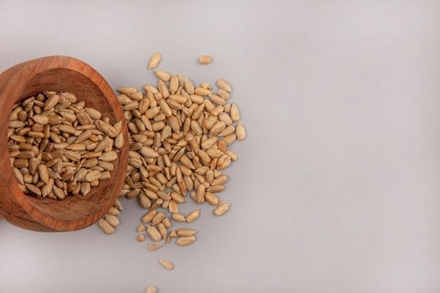 Vista dall'alto dei semi di girasole sgusciati organici che cadono da una ciotola di legno con lo spazio della copia