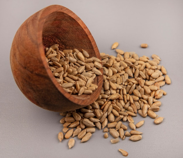 Top view of organic shelled sunflower seeds falling out of a wooden bowl