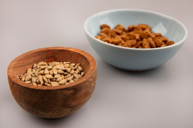 Top view of organic shelled sunflower seeds on a wooden bowl with tasty rye rusks on a bowl