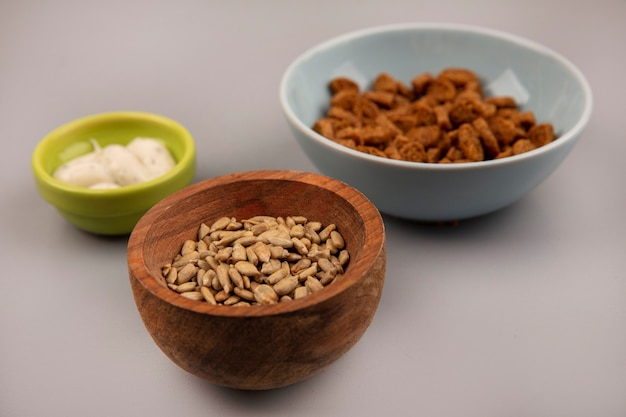 Top view of organic shelled sunflower seeds on a wooden bowl with tasty rye rusks with sauce