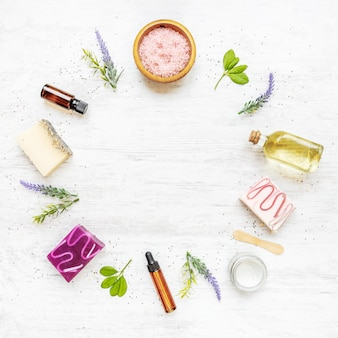 Top view of organic soaps and cosmetics arranged with lavender, herbs, chia seeds and essential oils.