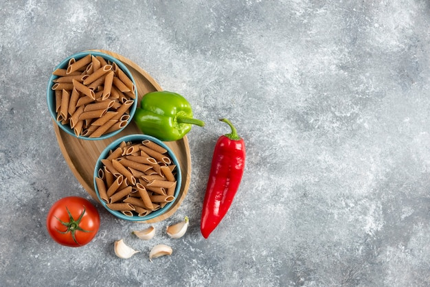 Top view of organic vegetables with raw penne pasta.
