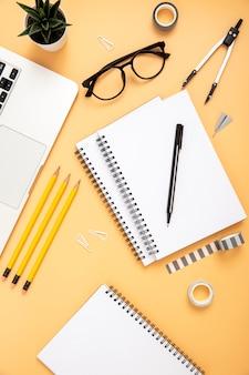 Top view organised arrangement of desk elements on orange background