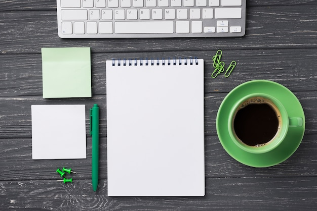 Top view of organized desk with coffee cup and sticky notes