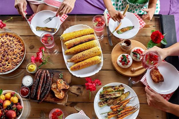 Вид сверху на обеденный стол, украшенный цветами, с посудой и едой. пикник на заднем дворе с друзьями или соседями, семейный ужин.