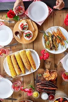 花で飾られたダイニングテーブル、食器、食べ物の上面図。友人や隣人との裏庭でのピクニック、家族との夕食。
