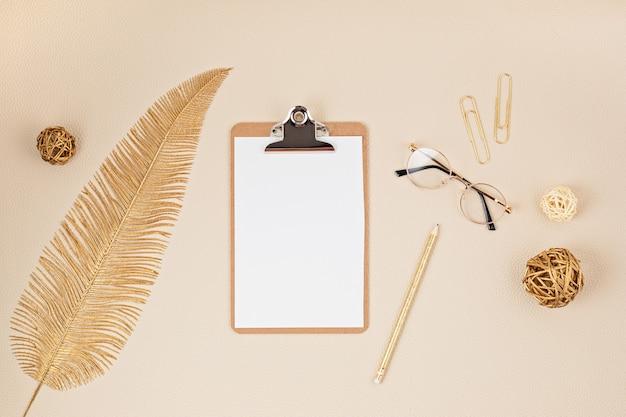 メモ帳、メガネ、金色のアクセサリーを備えたデスクトップの上面図。ホームオフィス、ビジネスウーマン、スタイリッシュなworkinfスペースのコンセプト。