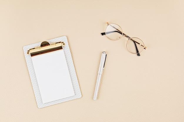 メモ帳、メガネを使用したデスクトップの上面図。ホームオフィス、ビジネスウーマン、スタイリッシュなworkinfスペースのコンセプト。フラットレイ、