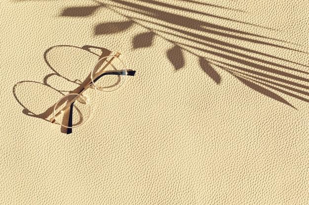 革の織り目加工の壁の上の夏の流行のメガネの上面図。夏のスタイル、休日、ファッション、コピースペースと旅行のコンセプト
