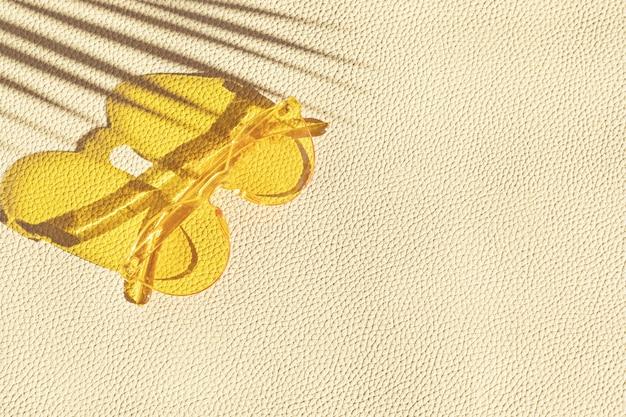 革の織り目加工の壁の上の夏の流行のサングラスの上面図。夏休み、パーティー、ファッション、旅行のコンセプト