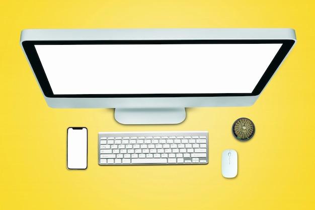 オフィススタイルの黄色の背景を持つタブレットスマートフォンコンピューターノートブックの上面図。
