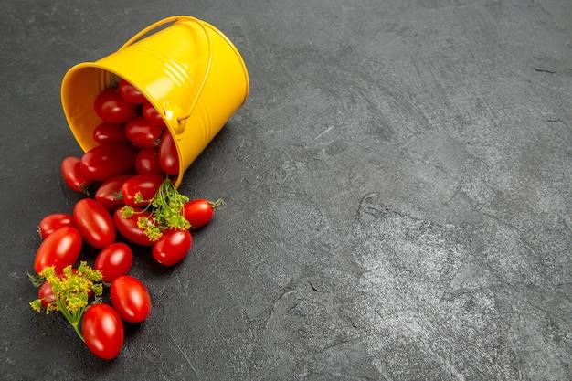 어두운 표면의 왼쪽에 체리 토마토와 딜 꽃으로 가득 찬 상위 뷰 뒤집힌 양동이