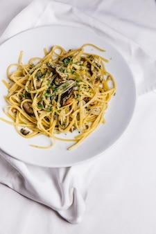 Top view of oyster spaghetti served in white plate on white tablecloth.