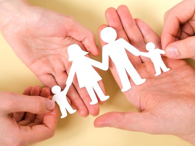Vista dall'alto p \ persone che tengono insieme in mano famiglia di carta carina