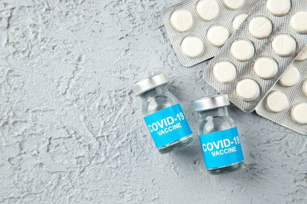 Top view of packed white pills and covid- vaccines on the left side on gray sand background with free space