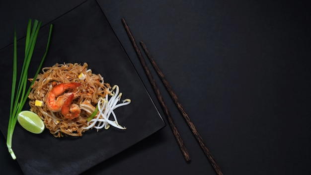 Top view of pad thai, stir fly of thai noodle with shrimp and egg in black ceramic plate on black table
