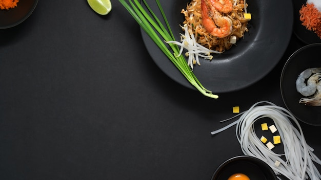 Top view of pad thai, stir fly of thai noodle with shrimp, egg, ingredients and seasoning  in black ceramic plate on black table
