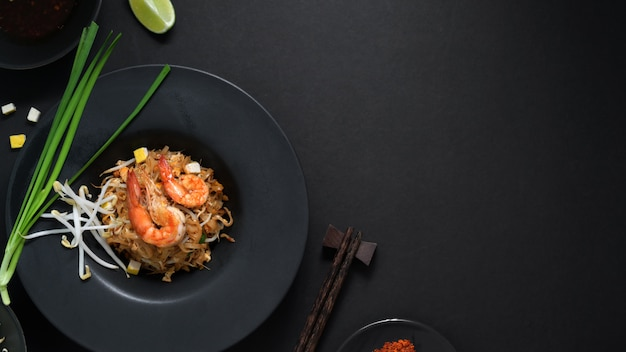 Top view of pad thai, stir fly of thai noodle with shrimp, egg and seasoning in black ceramic plate on black table