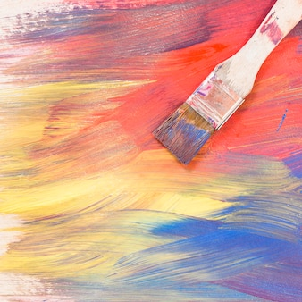 Top view of paint brush on bright colorful brush stroke textured