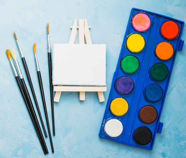 Top view of paint brushes; mini easel and watercolor palette