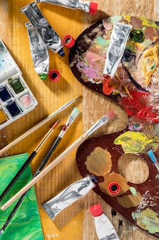 Top view of paint brushes with palette and paint