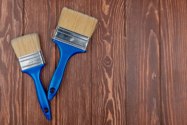 Top view of paint brushes on wooden background with copy space