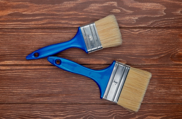 Top view of paint brushes on wooden background