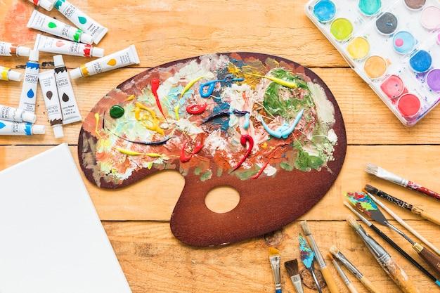 Tavolozza della vernice vista dall'alto circondata da materiale pittorico