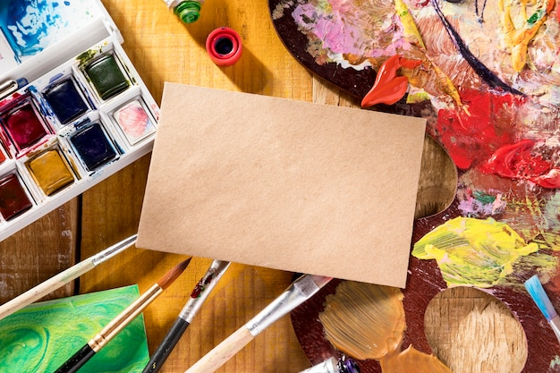 Top view of paint palette with brushes and paper